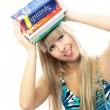 Blond girl holding a lot of book on her head - Stock Photo