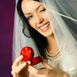 Beautiful happy bride holding a wedding ring - Stock Photo
