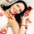 Brunette bride on the bed covered with rose leav - Stock Photo