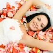 Brunette bride on the bed covered with rose leav — Stock Photo