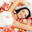 Brunette bride on the bed covered with rose leav — Stock Photo #1917643