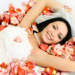 brunette bruid op het bed bedekt met roze leav — Stockfoto