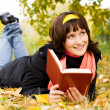 Stock Photo: Happy girl reading a book