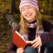 Laughing girl with a book — ストック写真
