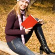 Stock Photo: Pretty girl reading book in park
