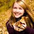 Pretty girl with yellow leaves in her hands — Stock Photo #1919753