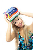 Blond girl holding a lot of book on her head — Stock Photo