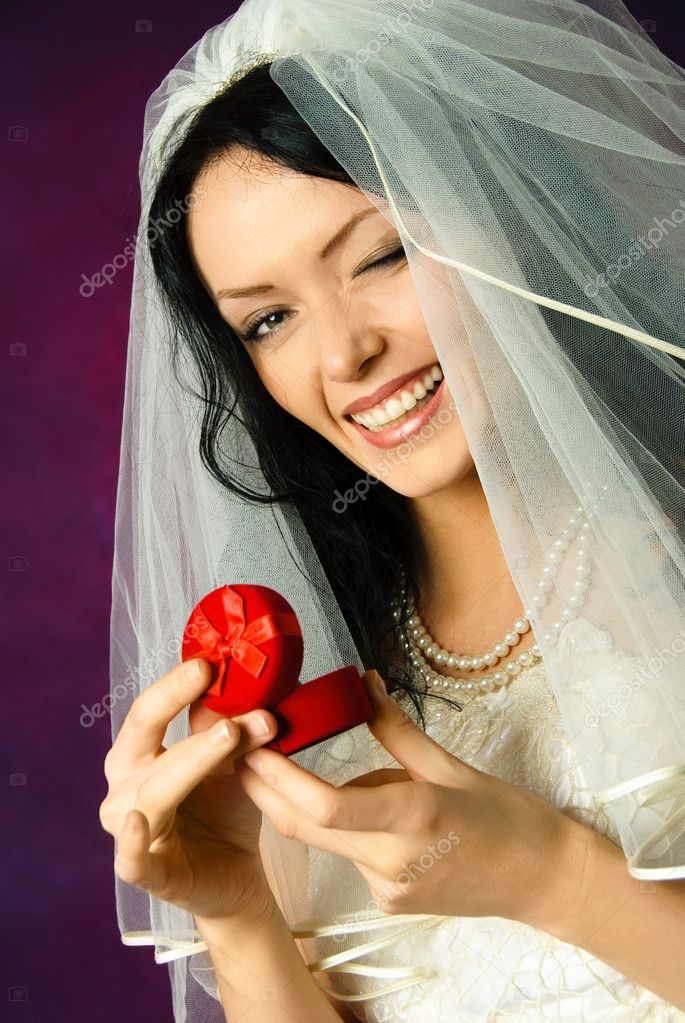 Studio portrait of a beautiful happy bride holding a wedding ring and winking ot us — Stock Photo #1917478