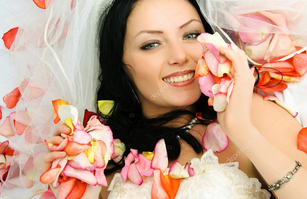 Happy beautiful brunette bride on the bed covered with rose leaves — Stock Photo #1917667