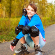 Pretty happy girl with rollerskates — Stock Photo