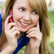 Beautiful girl with a cellphone outdoor — Stock Photo