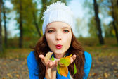 Pretty girl with yellow leaves in her hands — Stock Photo
