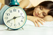 Beautiful sleeping woman with an alarm clock — Stock Photo