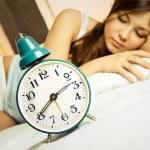 Sleeping woman with the alarm clock — Stock Photo