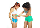 Women measuring waist with a tape — Stock Photo