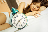 Sleeping woman with the alarm clock — Stock Photo