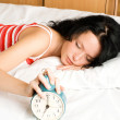 Beautiful brunette girl switches off the alarm c — Stock Photo