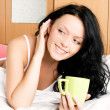 Royalty-Free Stock Photo: Girl with a cup of coffee in bed