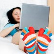 Young woman with a laptop on the bed — Stock Photo