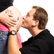 Father kissing his wife's belly — Stock Photo