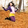 Happy jumping girl in the park - Stok fotoraf