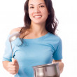 Beautiful girl with a serving spoon and pan in — Stock Photo #1994809