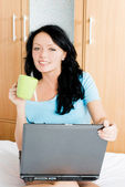 Cheerful girl with a laptop and a cup of coffee — Stock Photo