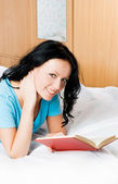 Beautiful girl reading a book on the bed — Stock Photo