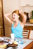 Laughing girl in the kitchen — Stock Photo