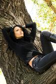 Beautiful sad girl on the tree — Stock Photo