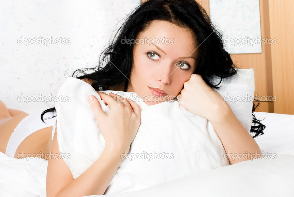 Beautiful thoughtful brunette woman with a pillow on the bed — Stock Photo #1995581
