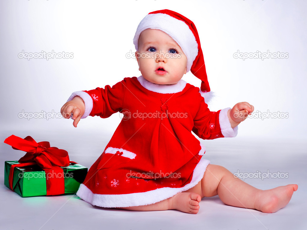 Little baby dressed as Santa sitting on the floor with Christmas presents — Stock Photo #1999156