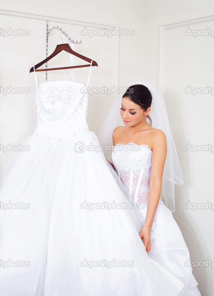 Pretty young woman is choosing a wedding dress in the shop   — Stock Photo #2001787