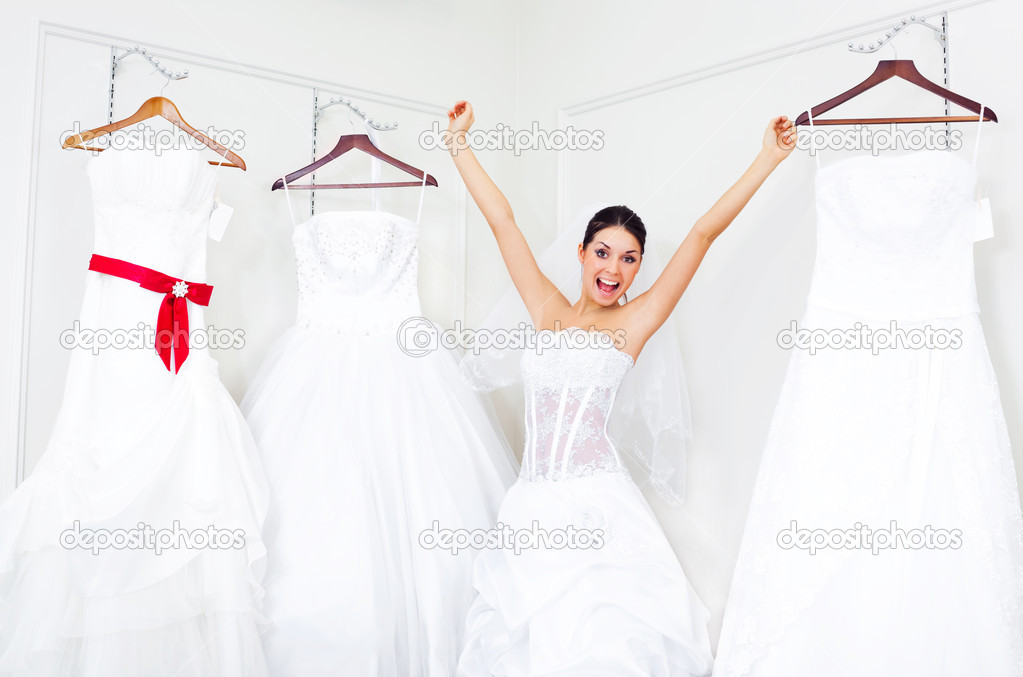 Pretty young excited woman is choosing a wedding dress in the shop   — ストック写真 #2001861
