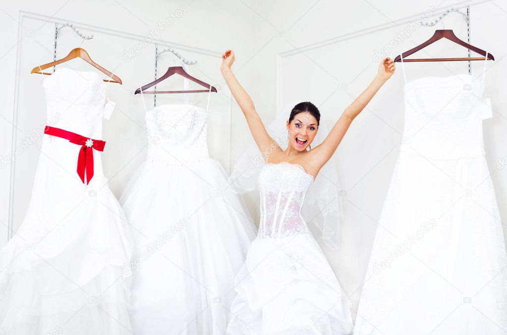 Pretty young excited woman is choosing a wedding dress in the shop   — Stock fotografie #2001861