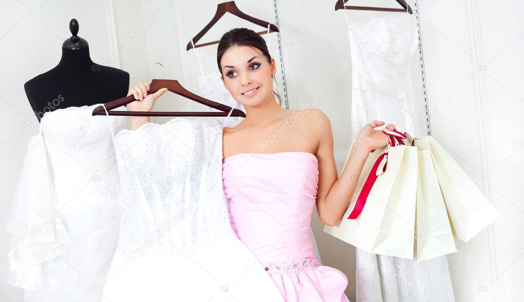 Pretty young woman is choosing a wedding dress in the shop   — Stock Photo #2001898