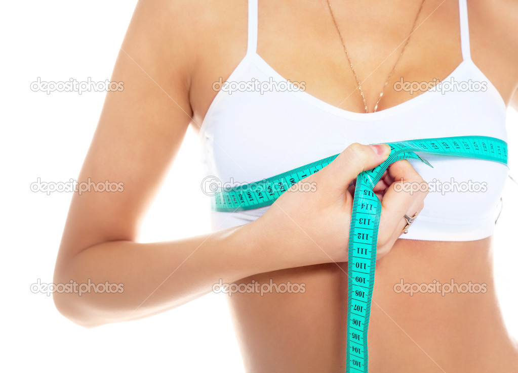 Young woman measures her breast with a measuring tape   Stock Photo #2237756