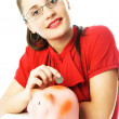 Stock Photo: Happy woman putting a coin into the piggy bank