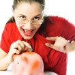 Excited woman putting a coin into her piggy bank — Stock Photo