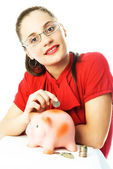 Happy woman putting a coin into the piggy bank — Stock Photo