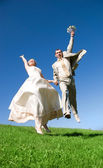 Happy jumping bride and groom on the hill — Stock Photo