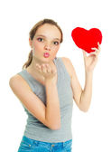 Girl with a heart-shaped pillow — Stock Photo