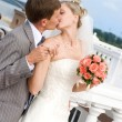 Foto Stock: Bride and groom kissing outdoor