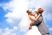Bruid en bruidegom kussen tegen blauwe hemel — Stockfoto