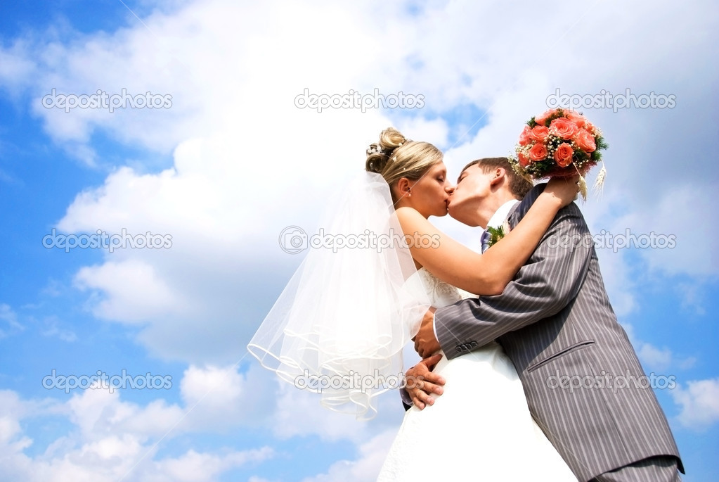 Young bride and groom kissing against blue sky with clouds — Stock fotografie #2605393