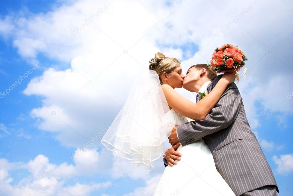 Young bride and groom kissing against blue sky with clouds — Stok fotoğraf #2605393