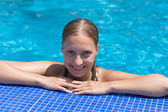 Wet blond girl in swimming pool — Stock Photo