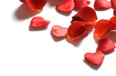 Rose petals and hearts on white backgrou — Stock Photo