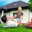 Happy family in front of the house — Stock Photo #2045156
