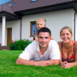 Happy family in front of the house - Stockfoto